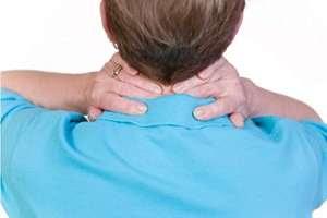 Una mujer se presiona detrás del cuello con las manos.