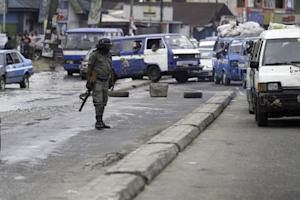 An armed policeman stands along Aba road as he monitors…