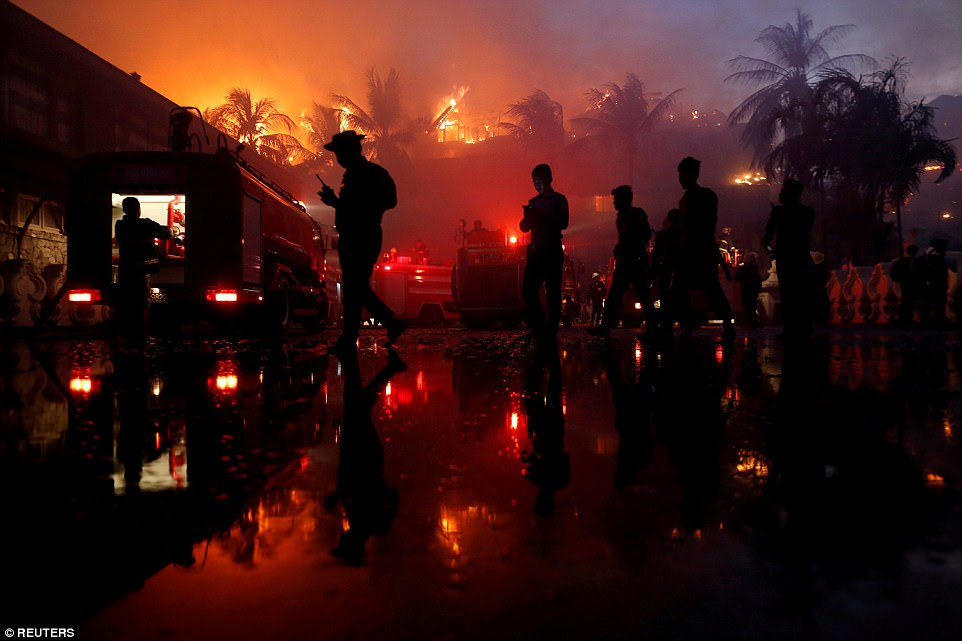 Police officers stand guard during a fire at Kandawgyi Palace hotel in Yangon, Myanmar, on October 19. The hotel was gutted by the fire, which fire fighters battled through the night