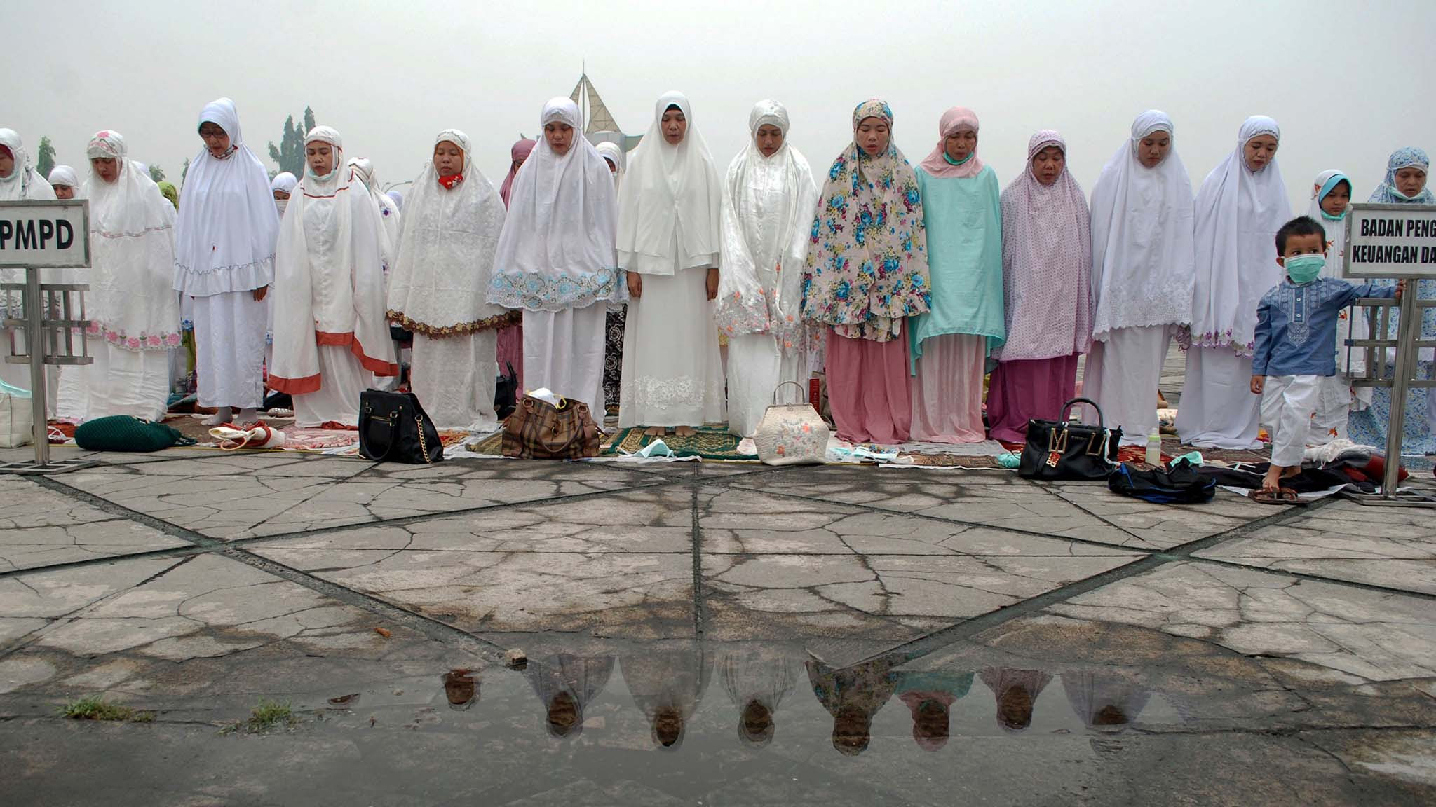 Muslim women pray for rain to put out the fires which enveloped the region in Pekanbaru, Riau province