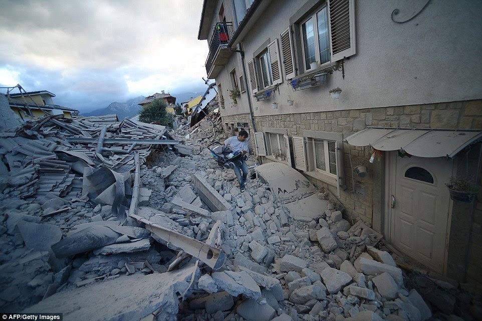 Dizimada: Um garras italianos carrinho de seu filho enquanto ele caminha sobre os escombros e detritos esquerda
