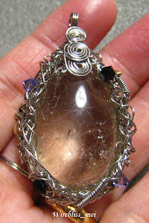 Wire wrapped entangled rutilated quartz pendant