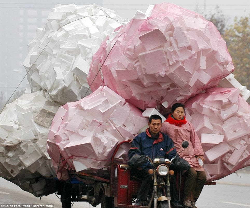 A man and his companion ride a tricycle engulfed by bags of plastic foam