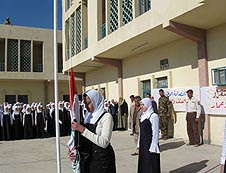Students proudly raise the Iraqi flag during the reopening ceremony of the Huda Girls School in Tarmiya, Iraq