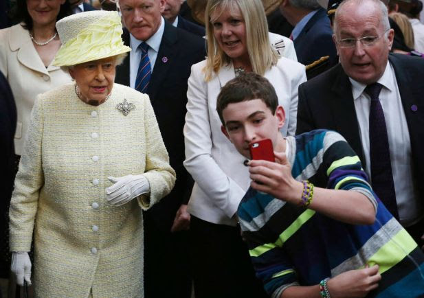 A local youth takes a selfie photograph in front of Queen Elizabeth II during a visit to St George's indoor market on in Belfast Tuesday June 24, 2014. The Queen is on a 3 day visit to Northern Ireland.