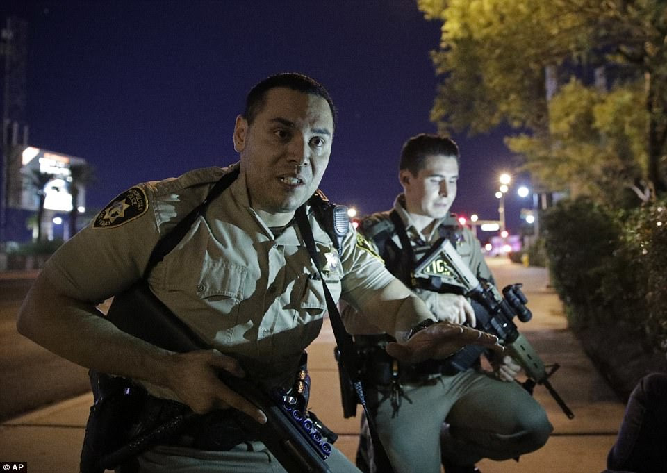 Police officers with shotguns and machine guns advised people to take cover near the scene of a shooting near the Mandalay Bay resort