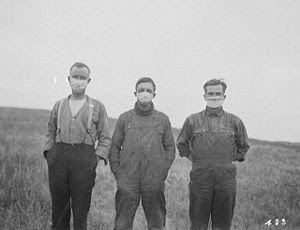 Men in an Alberta field wear masks during the ...