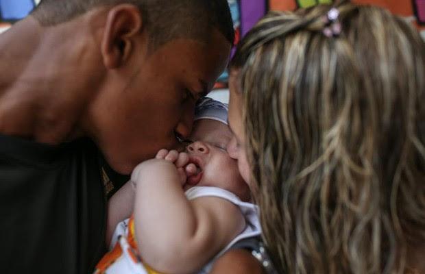 O pequeno Kauã, de 2 meses, e seus pais, Karine, de 16 anos, e Rafael, de 18  (Foto: Agência EFE)