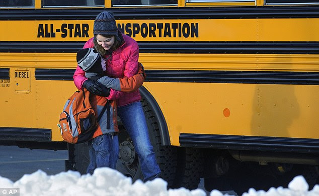 Keeping them close: A woman hugs a young boy, who had attended Sandy Hook school, before he boards a bus to a newly set-up school in neighboring Monroe, Connecticut