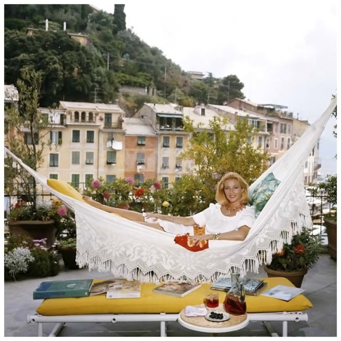 Daniela Bianchi poses in a hammock on the terrace of her apartment in Portofino, Italy, in August 1977, photo by Slim Aarons
