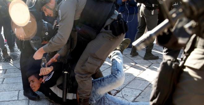 Un policía israelí detiene a un joven palestino cerca de la Puerta de Damasco, en Jerusalén, tras la oración del viernes. REUTERS/Ronen Zvulun