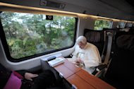 In this photo provided by the Vatican newspaper Osservatore Romano, Pope Benedict XVI, right, reads as he travels for a meeting in Assisi, central Italy, Thursday, Oct. 27, 2011. Buddhist monks, Muslim imams, Orthodox patriarchs and Yoruba leaders have flocked with Pope Benedict XVI to the Umbrian hilltown of Assisi to make an interfaith call for peace and insist that religion must never be used as a pretext for war. (AP Photo/Osservatore Romano) EDITORIAL USE ONLY