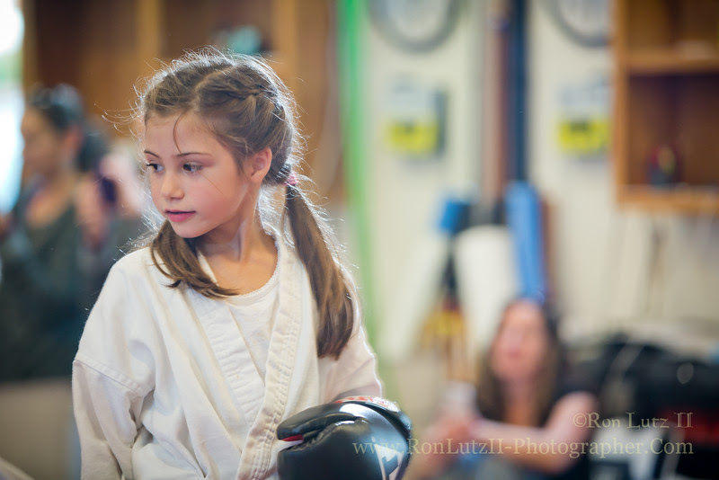 Freja prepares to demonstrate Muay Thai punching and kicking during her belt advancement test. Her favorite part? Getting to wear her mouth guard.