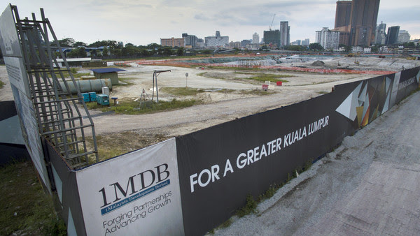 Signage for 1Malaysia Development Bhd. (1MDB) is displayed at the site of the Tun Razak Exchange (TRX) project in Kuala Lumpur, Malaysia, on Friday, July 17, 2015. As Malaysia Prime Minister Najib Razak faces an investigation sparked by a Wall Street Journal report that $700 million may have wended its way into his personal bank accounts, the ruling coalition has swiftly closed ranks around him. The probe has sparked a raid on the state investment company 1MDB whose advisory board Najib chairs, and spurred calls to resign from opposition lawmakers. Photographer: Goh Seng Chong/Bloomberg
