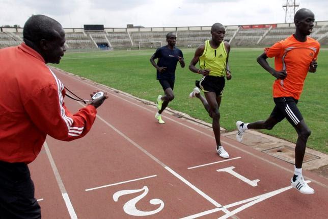 Kenya's National Athletics head coach Julius Kirwa (L) looks at his watch as athletes run during a training session at Nyayo National Stadium ahead of the Beijing 2008 Olympic Games in the capital Nairobi July 25, 2008.   REUTERS/Antony Njuguna/Files