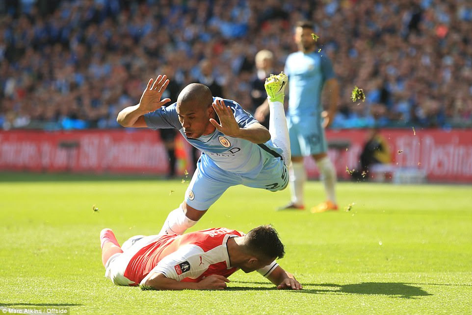 Fernandinho, the City midfielder, takes a tumble after a robust challenge from Sanchez  just before the half hour mark