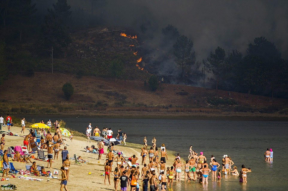 Em Pontevedra, na Galiza, no noroeste da Espanha, perto da fronteira com Portugal, os turistas romper com a natação e banhos de sol para contemplar os incêndios se espalhando por todo o morro