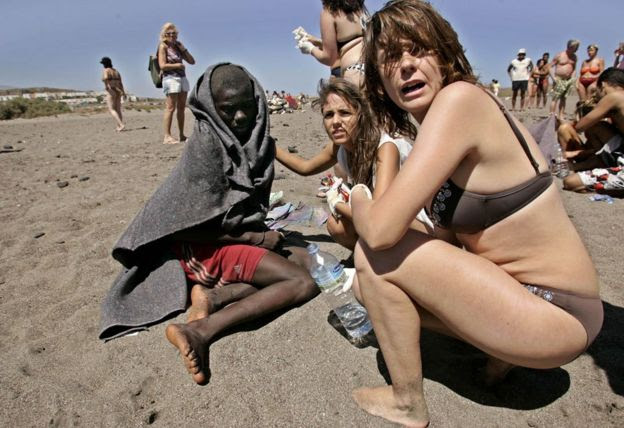 Tourists help a migrant boy on La Tejita beach, Tenerife