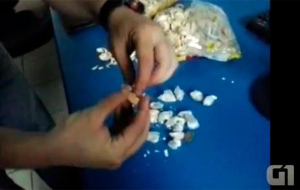 Um a um os pacotes de droga foram colocados entre as camadas das bolachas (Foto: Reprodução/Vídeo cedido ao G1 pela Coape)