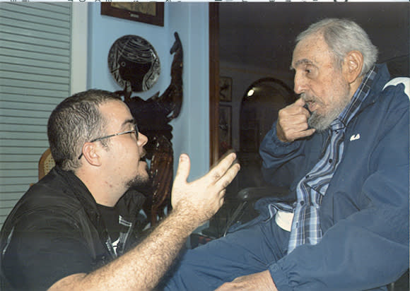Former Cuban President Fidel Castro talks to President of Cuba's University Students Federation Randy Perdomo during a meeting in Havana