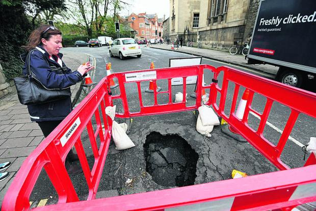 Oxford Mail: Alison King-Smith snaps a picture of the hole