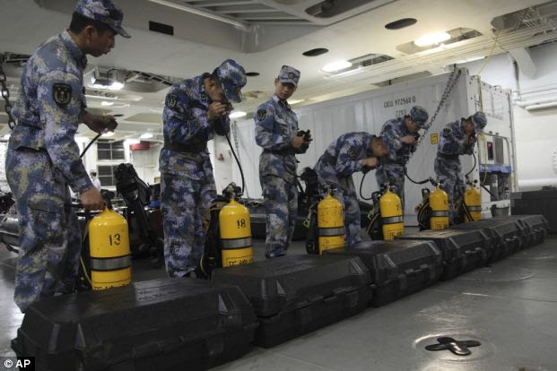 Chinese sailors check equipment before taking part in search efforts for the missing Malaysia Airlines passenger jet onboard the Jinggangshan amphibious docking ship while in Sanya in south China's Hainan province