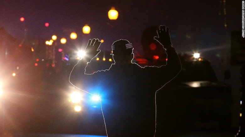 In 2014, a protester stands in front of police vehicles in Ferguson, Missouri.