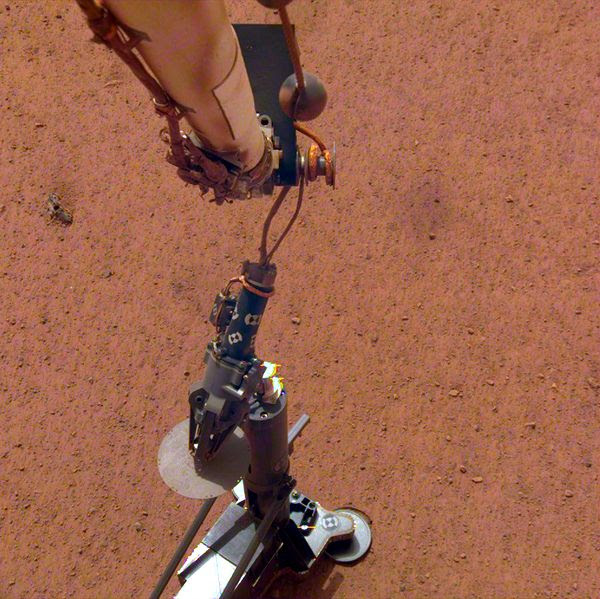 An image of the InSight lander's robotic arm placing the Heat Flow and Physical Properties Package on the surface of Mars...on February 12, 2019.