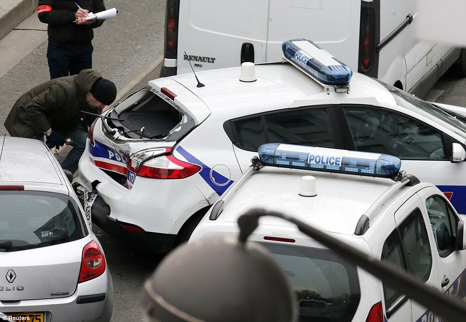 Trail of destruction: Police inspect the damage after a collision between police cars at the scene during a firefight with Islamic militants