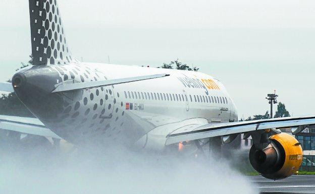 Una de las aeronaves de Vueling maniobra en la pista mojada del aeropuerto de Hondarribia.