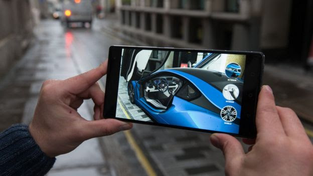 Man holding smartphone showing virtual BMW car in a street