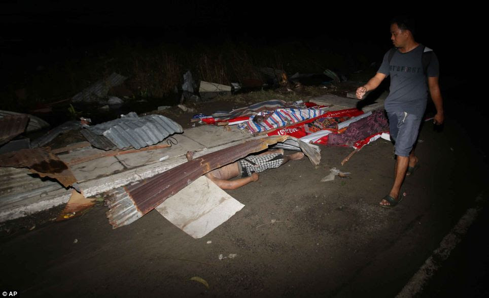 Victim: A resident walks past dead bodies that lie on the street in Tacloban city, Leyte province