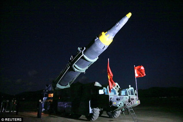 North Korean leader Kim Jong Un inspects the long-range strategic ballistic rocket Hwasong-12 ahead of the launch