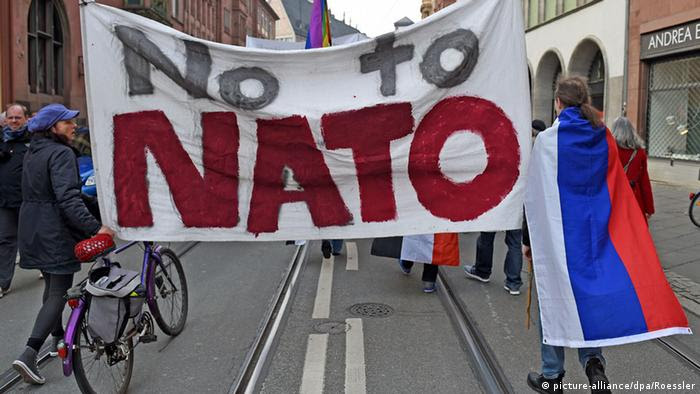 Demonstrators with a flag that reads No to NATO in Frankfurt am Main