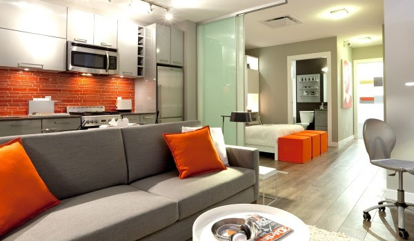 When home has an open floor plan, it is important that rooms are divided but still have a unifying design feel. Here, a bright orange backsplash is a dramatic focal point in the kitchen, while accent pillows on the couch tie everything together without being cartoonish.