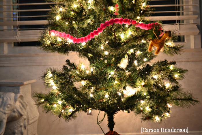 lower-portion-of-fake-christmas-tree-pink-garland-giraffe-ornament
