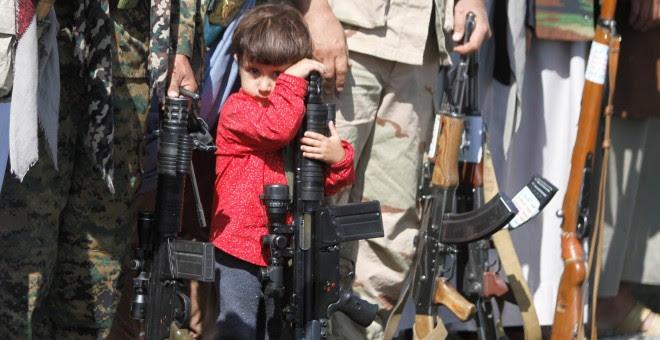 Un niño descansa apoyado sobre un arma en Yemen./REUTERS