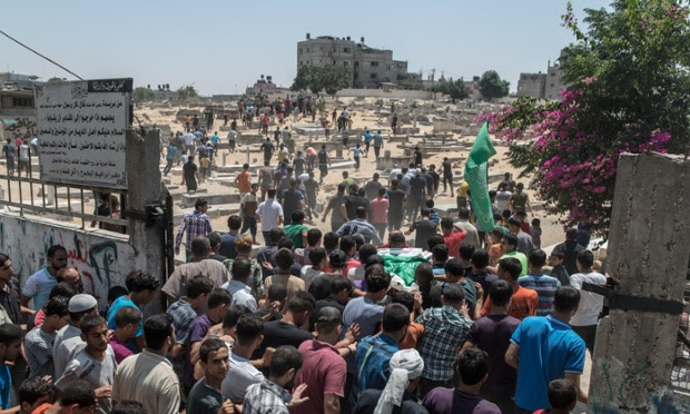 Crowds carry Rahed Taysir al-Hom to be buried next to his brother in the Gaza cemetery of Jabaliya.