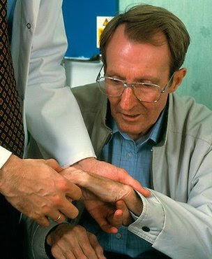 A doctor examines the hands of a man with Parkinson's disease