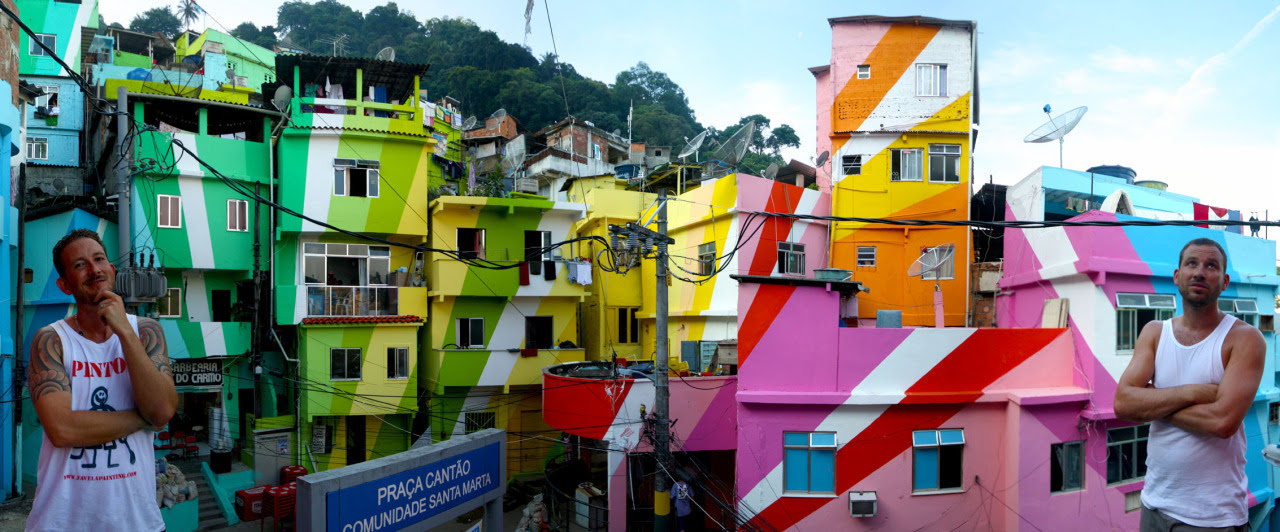 "Praça Cantão, Communidade Da Santa Marta, Rio De Janeiro Using a flexible concept of colourful rays which can easily be expanded, we made a design for the houses around the square and part of the street, including the local Sambaschool. A group of local inhabitants where instructed by trainers from TintasCoral as part of the project ""Tudo de Cor para Santa Marta."" They where taught everything from different types of paint to safety measures about working on scaffolding. As every wall, every house needs another solution, the painters learn to work with all kinds of material. During the hard month of work they received an education as well as a paycheck. The final result was a huge artwork spanning over 34 houses. It's our goal to attract enough funds to return to Rio later this year to continue working on the project, as our dream has always been to paint an entire hillside favela. This project Back to Rio could turn the community into one of the greatest community driven artworks of our time. image by Douglas Engle"