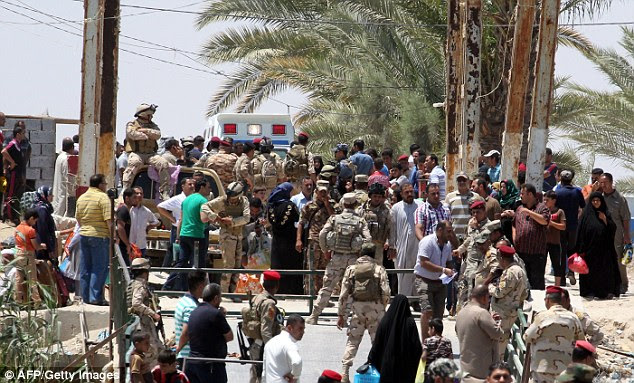 Muhannad Haimour, spokesman and adviser to the governor in the province of Anbar, said 'Ramadi has fallen' to ISIS. Pictured: Displaced Iraqis from Ramadi gather as they flee their hometow