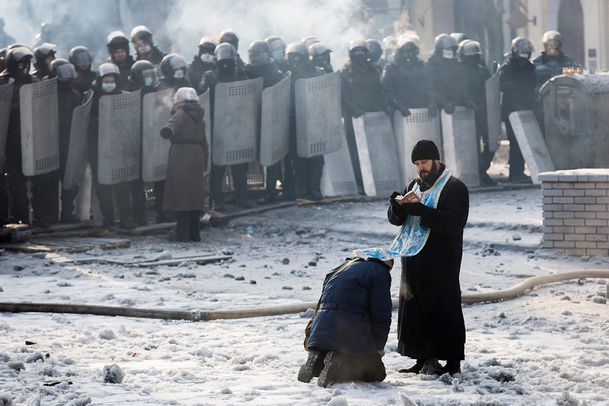 A man kneels before an Orthodox priest in an area separating police and anti-government protestors near Dynamo Stadium on January 25, 2014 in Kiev. (Rob Stothard/Getty Images)