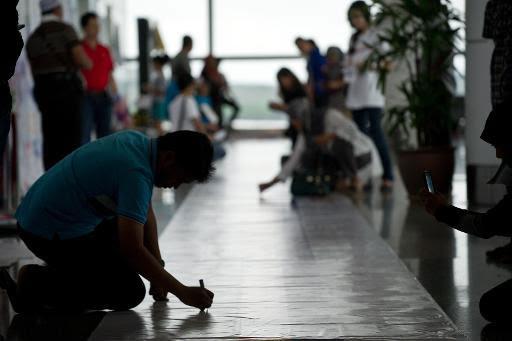 Visitantes escrevem mensagens para os passageiros do avião desaparecido, no Aeroporto Internacional de Kuala Lumpur. Foto: Mohd Rasfan/AFP