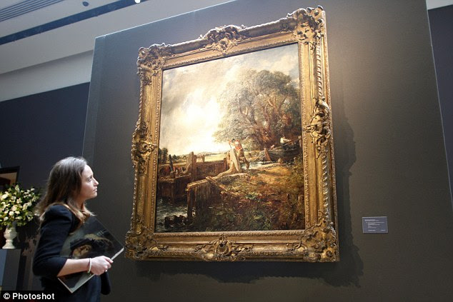 Beauty of a bygone age: A Christie's employee gazes at The Lock by English artist John Constable as it went up for auction yesterday