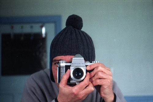 reflected self-portrait with Praktica IV camera and knitted hat by pho-Tony