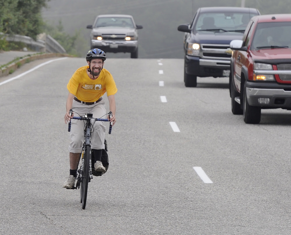 "John Brooking ""controls the lane"" near the Maine Mall in South Portland. He and other bicycle educators say riding near the middle of the road is sometimes necessary for safety."