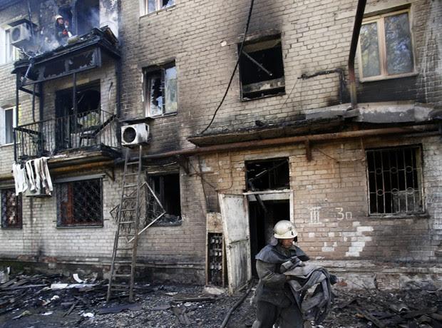 Bombeiros trabalham em edifício incendiado após bombardeio na cidade de Donetsk, leste da Ucrânia (Foto: Darko Vojinovic/AP)