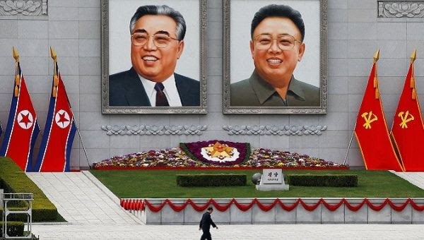 A man walks in front of portraits of North Korea founder Kim Il Sung and late leader Kim Jong Il in central Pyongyang