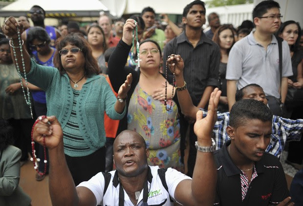 Fiéis concentram-se em frente a suposta imagem da Virgem Maria neste domingo (11) em subúrbio de Kuala Lumpur (Foto: Reuters)