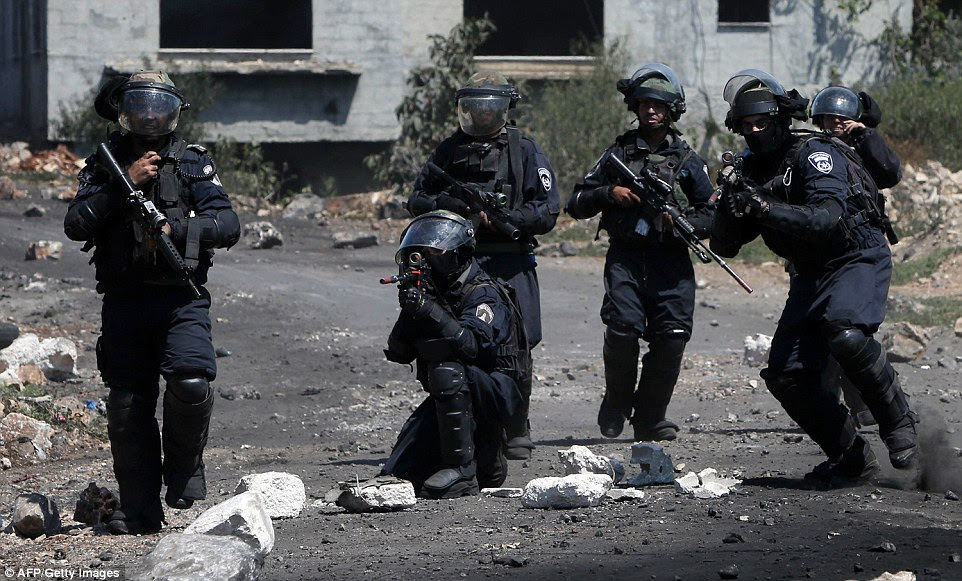 Members of Israeli security forces aims their weapons towards Palestinian stone throwers during clashes following a demonstration against the expropriation of Palestinian land by Israel in the village of Kafr Qaddum, near Nablus in the occupied West Bank